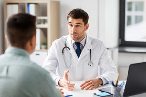 doctor explaining men's addiction treatment center in NH to male client